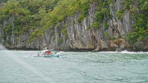 """A banca returning to Sabang in front of the nearest cliff to the cave's mouth"" retirednoway"