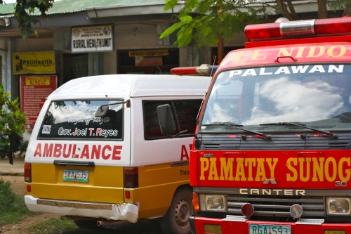 """Circumcision normally costs 500 pesos per child and would have been performed at the government clinic shown in the background, the ""rural health clinic."" It has been the habit of politicians to plaster their name on their projects. I can tell, therefore, that the ambulance was procured under the administration of the former disgraced governor. (Joel T. Reyes is currently a fugitive. He chose not to surrender to authorities to answer charges that he is responsible for ordering the assassination of one of his critics. Read more below for this digression. The advantage, and disadvantage, of affixing one's name to public property--even if it was that person's project--is laid bare here!)"" retirednoway"